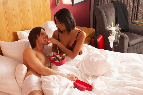 Woman feeding man Valentine's candy in bed